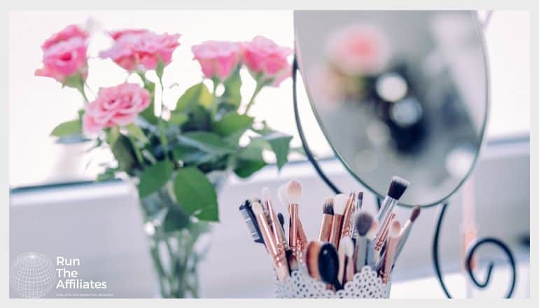 container of make-up brushes next to a mirror in front of a vase of pink roses