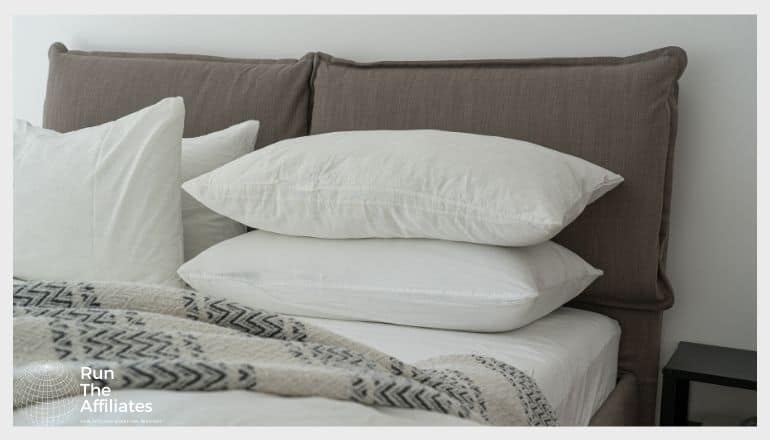 stack of white pillows on a grey bed