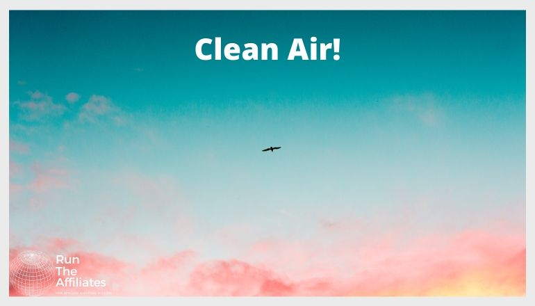 """pink clouds against a blue sky with a solitary bird flying. The words """"clean air!"""" are written across the top of the image"""