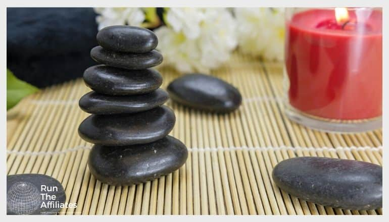 smooth black rocks stacked next to a red lit candle