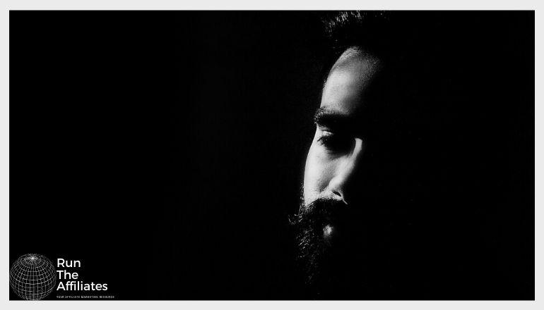 bearded man against a dark black background