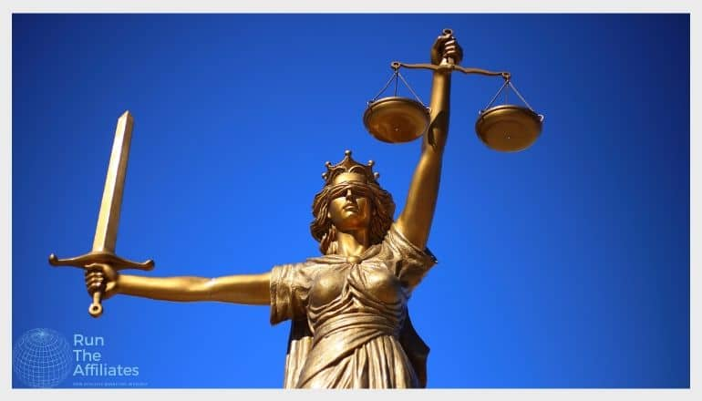 bronze lady justice holding a sword and scales against a deep blue sky background