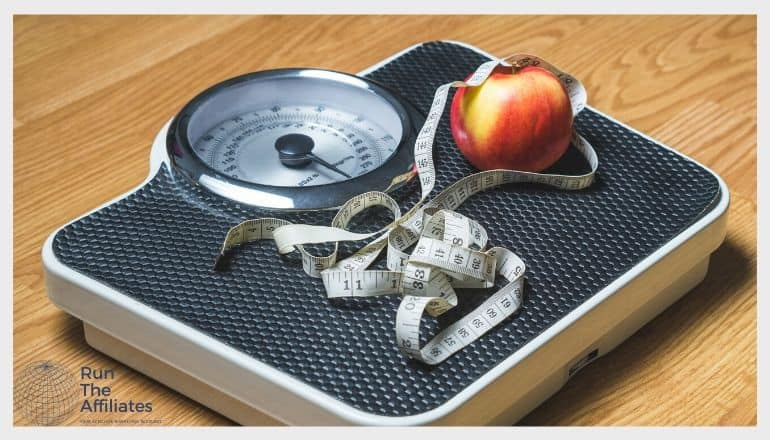 a red apple and a measing tape on a weight loss scale