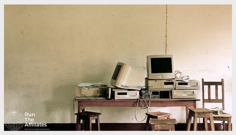 Old computer hardware and CRT monitors on a wooden desk with stools and chairs in the foreground