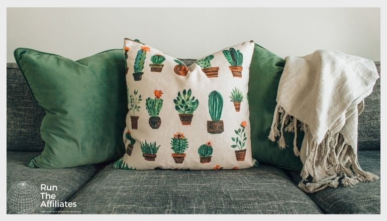 2 green throw pillows and a cactus themed pillow on a grey sofa with a white blanket draped over the back of the sofa