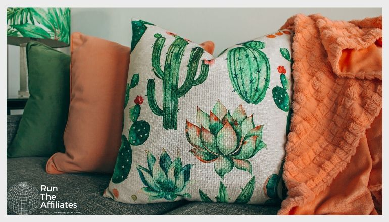 green and orange throw pillows with an orange blanket draped over a sofa