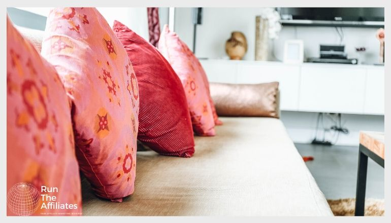 a row of pink and red throw pillows on an off-white sofa