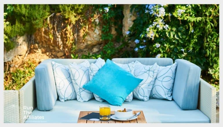 blue throw pillows on a blue sofa with tropical plants behind it