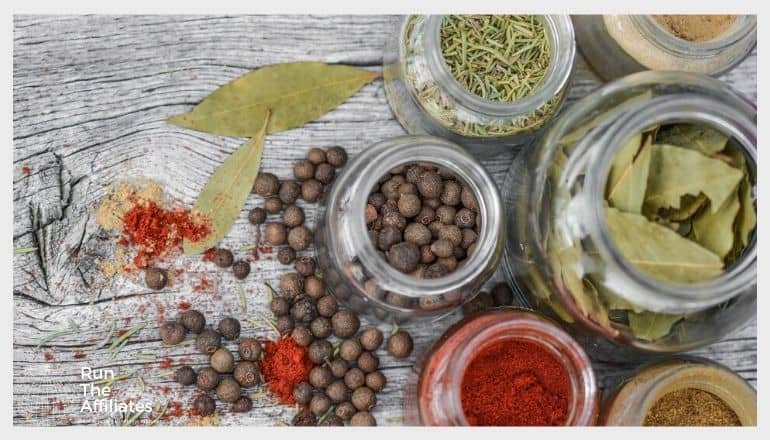 spices and herbs in mason jars sitting on a table