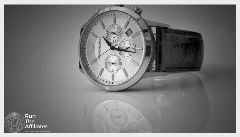 silver watch with dark band setting on a reflective surface
