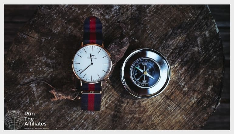 watch with red and black band sitting on a piece of wood next to a compass