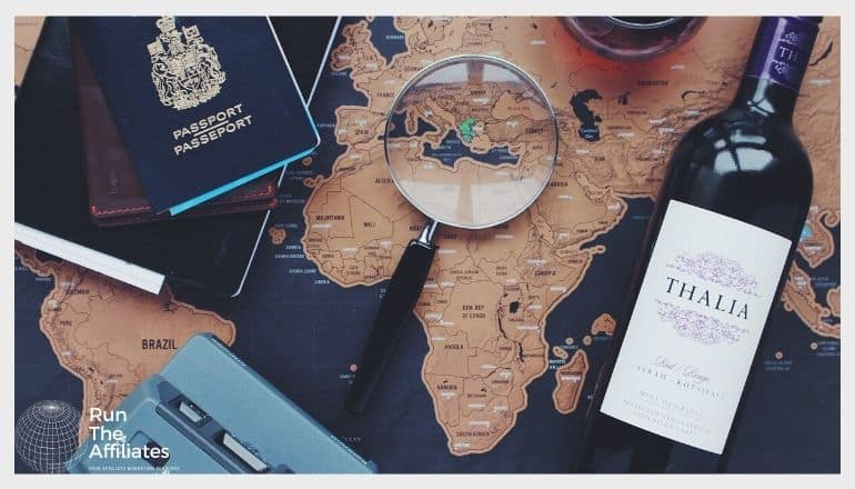 map on a table with a magnifying glass, passport, camera and a bottle of wine on top of it