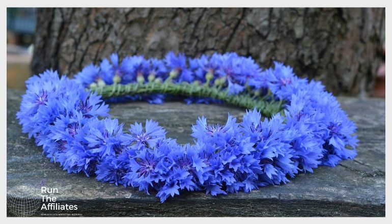 wreath made of blue flowers laying on a rock