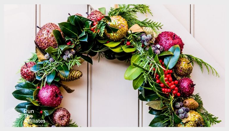 wreath hanging on a door. the wreath is made of leaves and fruit