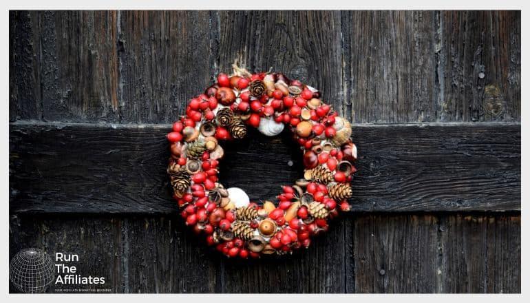 red wreath hanging on a wood door