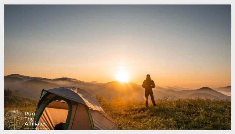 man camping at dawn with a tent in the forground and the rising sun in the background