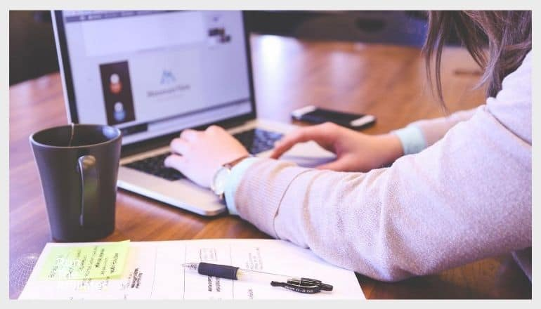 woman working on a marketing plan while sitting in from of a laptop