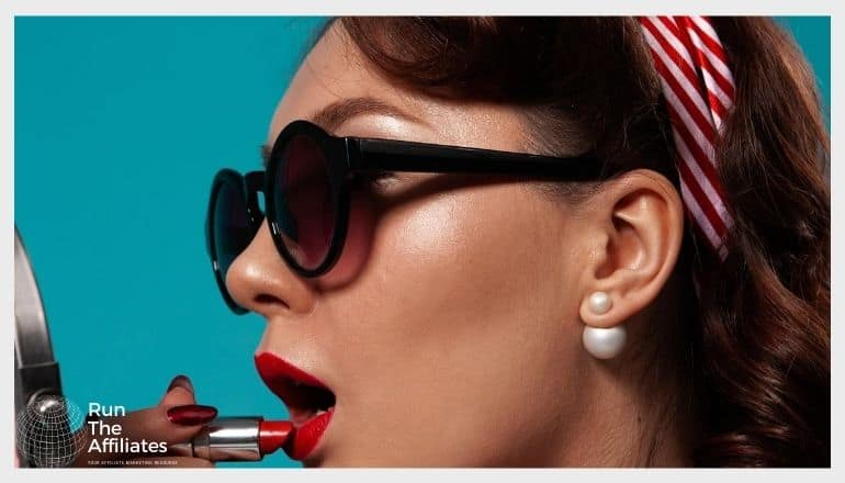 woman wearing sunglasses while applying red lipstick