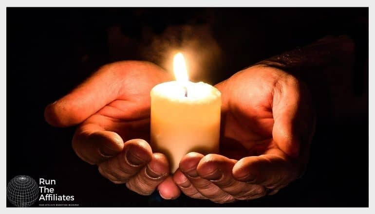 two hands illuminated by the candle in their palms