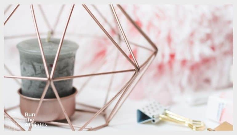 candle in a copper holder surrounded by a copper geometric shape