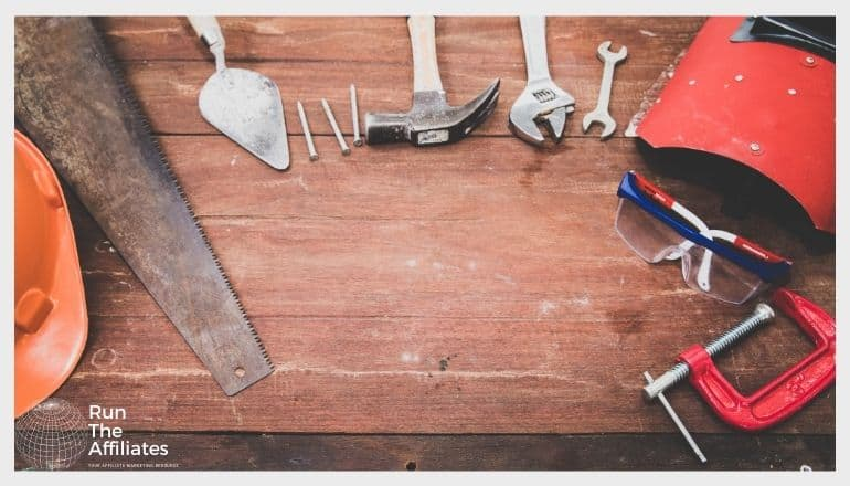 hammer saw wrench and other assorted tools laid out on a wooden table image from above