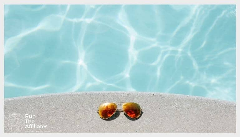 top down view of sunglasses resting next to a pool