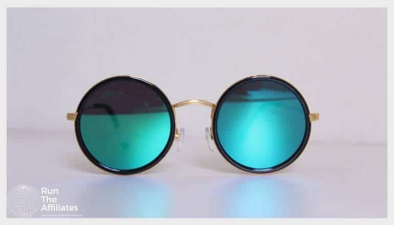 round blue tinted sunglasses sitting on a white table