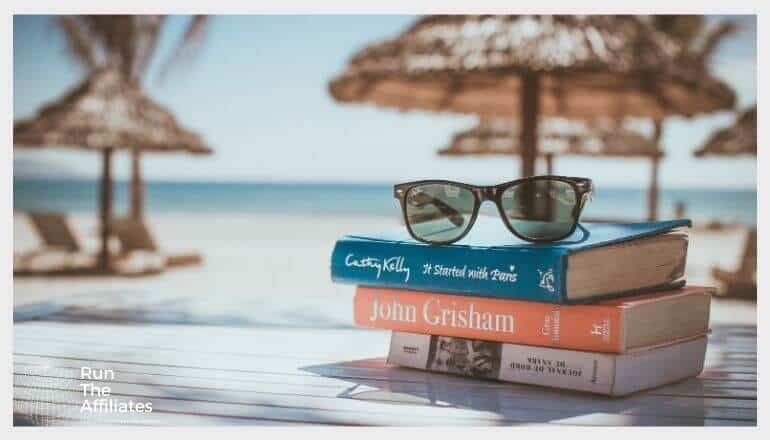 sunglasses resting on a stack of books near a beach resort