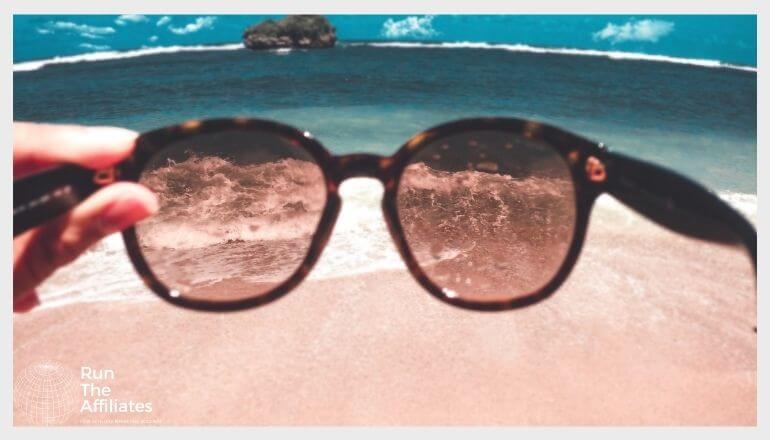 looking through a pair of sunglasses at a beach coastline