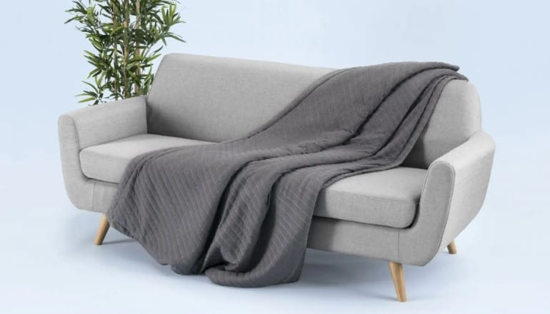 grey honeybird weighted blanket resting on a light grey sofa with a green plat in the background