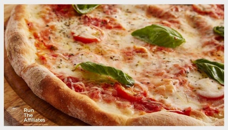 close up of a pizza with tomatoes and green basil leaves