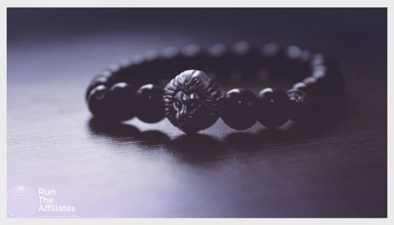 black bracelet with a lions head stone resting on a black table