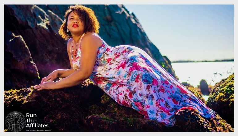 woman in a floral dress posing on a rock on the beach at sunset