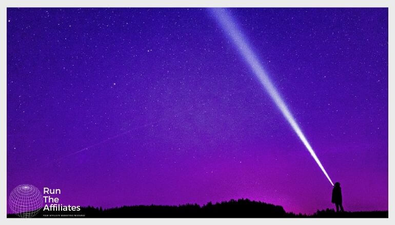 man shining a flashlight into the night sky