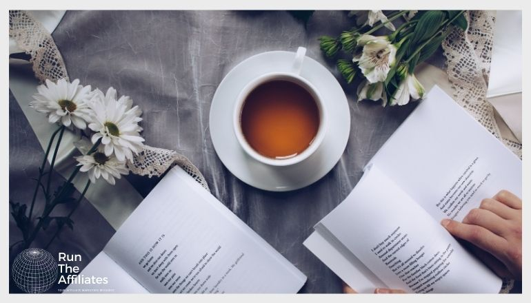 cup of tea on a table surrounded by open books and flowers