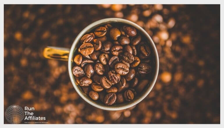 coffee cup filled with coffee beans on a bed of coffee beans