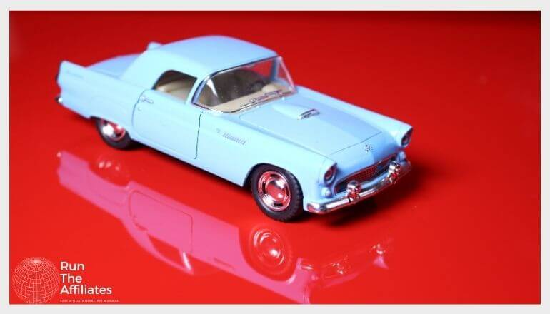 blue diecast car on a glossy red tabletop