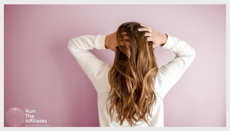 woman running her fingers through here hair facing away from the camera