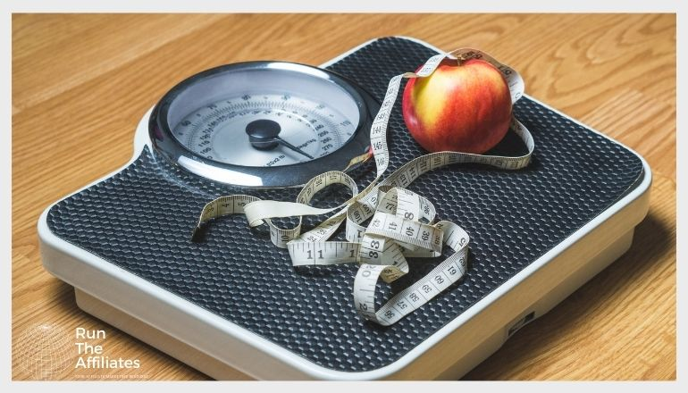 scale with an apple and tape measure on it