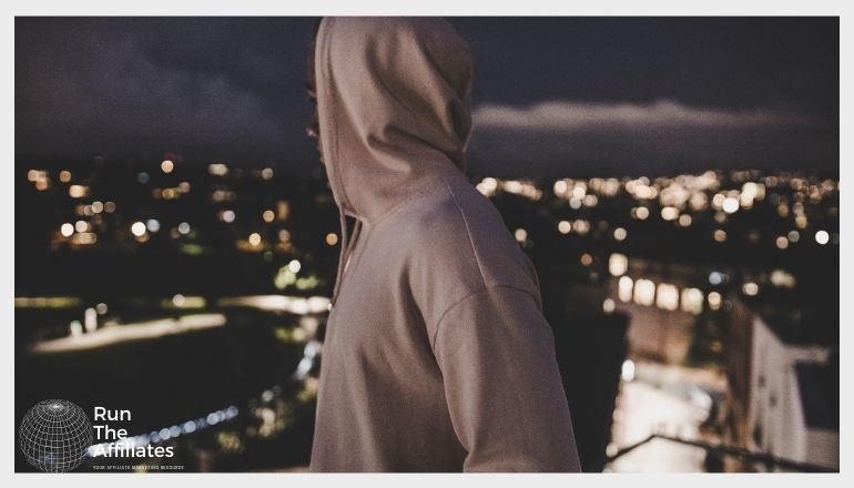 man in a hoodie overlooking an urban cityscape