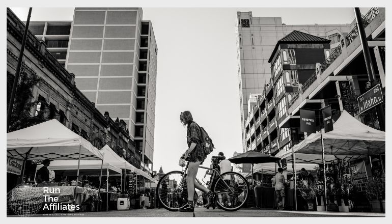 black and white photo of man on bike in the city
